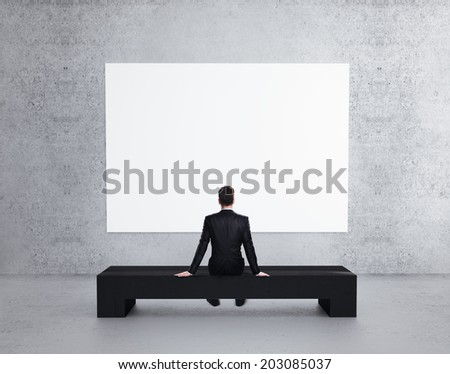 businessman looking to blank poster  on wall - stock photo