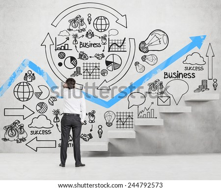 businessman looking to drawing business scheme on wall - stock photo