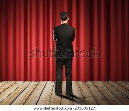 businessman looking to red curtains in room - stock photo
