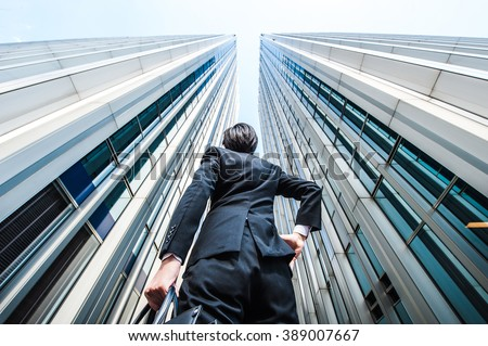 Businessman looking up at the high building, low angle - stock photo