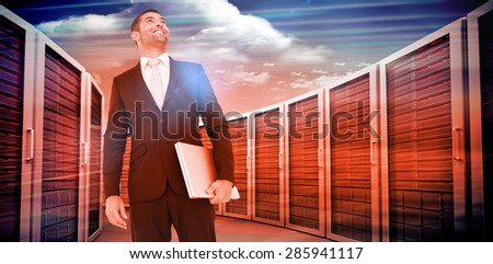 Businessman looking up holding laptop against composite image of server towers - stock photo
