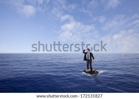 Businessman lost at sea inside a travel bag - stock photo