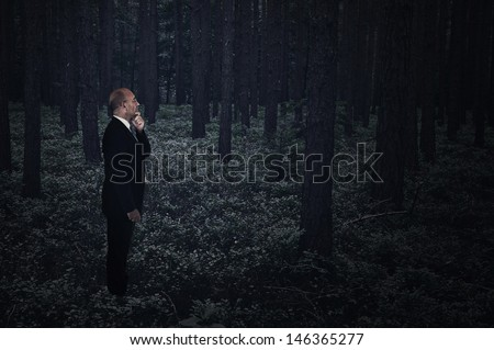 Businessman lost in a dark creepy forest at midnight - stock photo