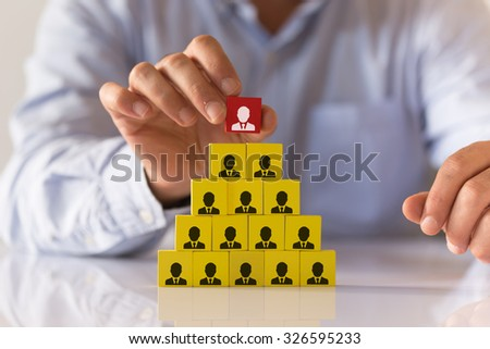 Businessman Making a Business Team Pyramid with Colorful Wooden Cubes - stock photo