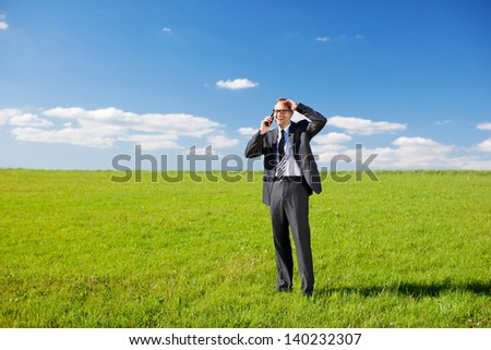 Businessman making a call on his mobile standing in the middle of a lush green field under a sunny blue sky - stock photo