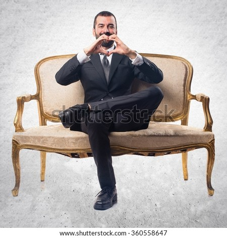 Businessman making a heart with his hands - stock photo