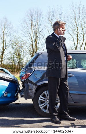 Businessman Making Phone Call After Traffic Accident - stock photo