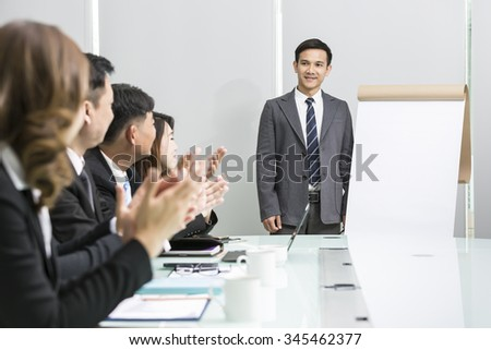 Businessman making presentation in bright office with a blank board for copyspace - stock photo