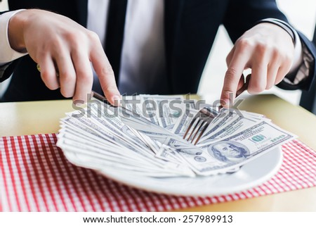businessman male eating his money, concept. eats dollars. - stock photo