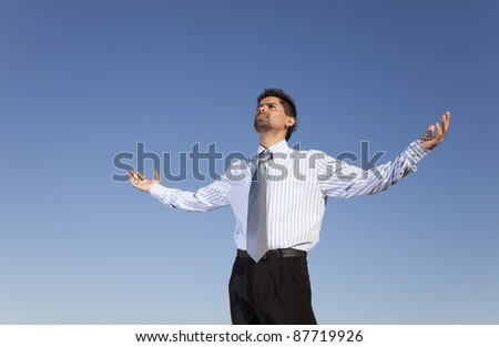 Businessman man looking to the sky with his arms outstretched - stock photo