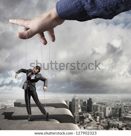 Businessman marionette on ropes controlled by puppeteer against city background - stock photo