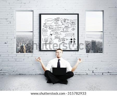 businessman meditating in loft, business concept - stock photo