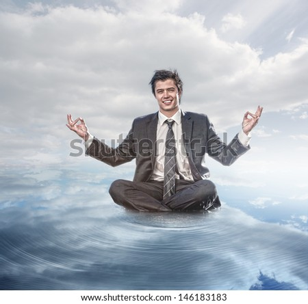 Businessman meditating on the water - stock photo