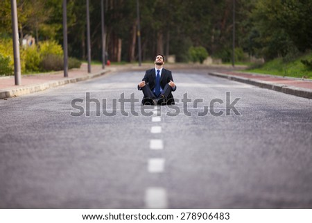 Businessman meditating sit in the middle of the street - stock photo