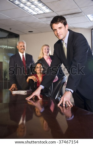 Businessman meeting in boardroom with multiethnic colleagues - stock photo