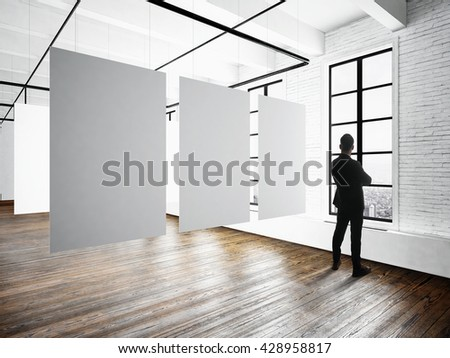 Businessman Modern museum expo loft interior.Open space studio.Empty white canvas hanging.Wood floor,bricks wall,panoramic windows.Blank frames ready for bussiness information.Horizontal mockup - stock photo