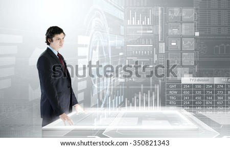 Businessman near table over virtual interface background - stock photo