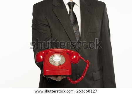 businessman offering assistance holding a red vintage telephone - stock photo