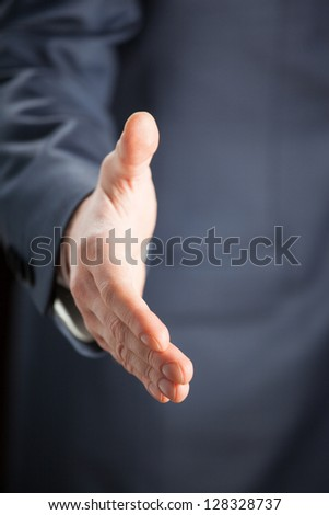 Businessman offering handshake to you - closeup shot - stock photo
