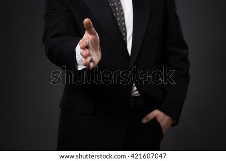 Businessman offering his hand for handshake. Greeting or congratulating gesture. Business meeting and success. - stock photo