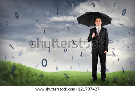 Businessman on a field with binary code falling - stock photo