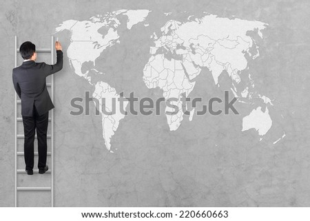 Businessman on a ladder drawing a world map on concrete wall with chalk  - stock photo