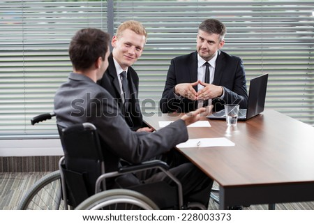 Businessman on a wheelchair sitting at the table with his colleagues - stock photo