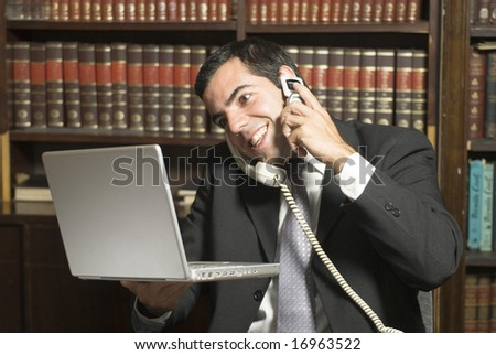 Businessman on cell phone in office holding computer. Horizontally framed photo. - stock photo