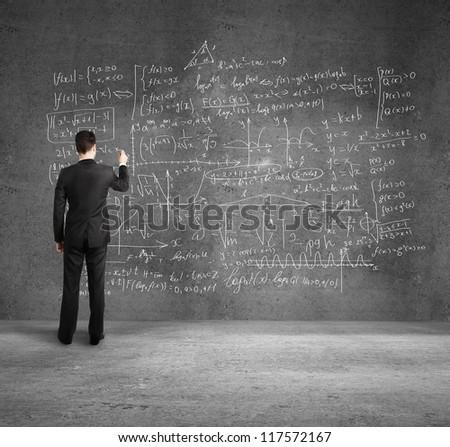 businessman  on  desk drawing formulas - stock photo