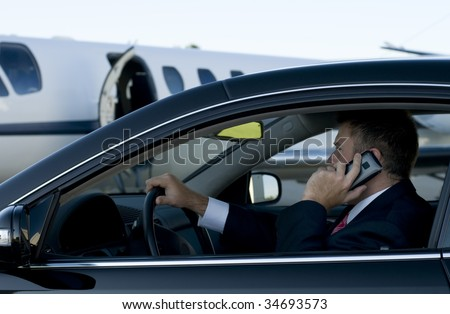Businessman on his cell phone in his luxury car in front of a corporate jet - stock photo