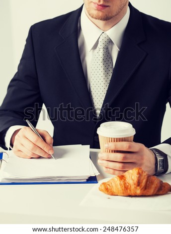 businessman on his coffee break making notes - stock photo