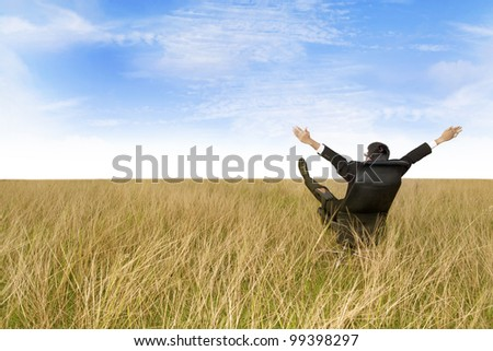 Businessman on his office chair with his arms and feet up in the air. Shot outdoor in marshes - stock photo