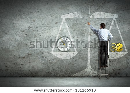 Businessman on ladder pointing at scale picture - stock photo