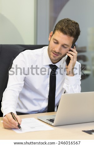 Businessman on mobile phone in office - stock photo