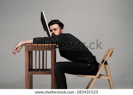 Businessman on monitor of computer on gray background - stock photo