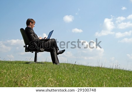 Businessman on office chair working with a laptop outdoor - stock photo