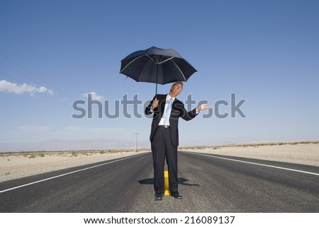 Businessman on open road in desert with umbrella, feeling for rain, low angle view - stock photo