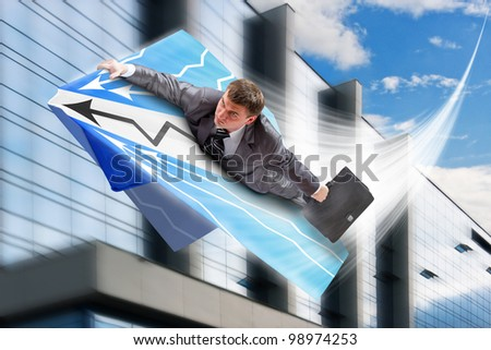 Businessman on paper airplane flying over downtown - stock photo