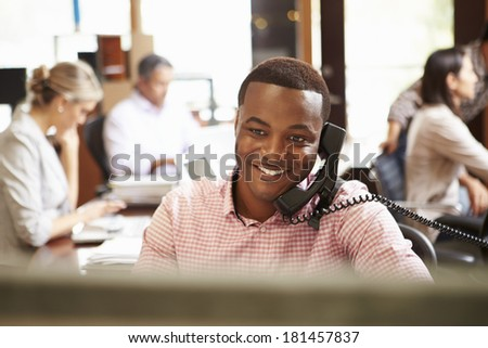 Businessman On Phone At Desk With Meeting In Background - stock photo