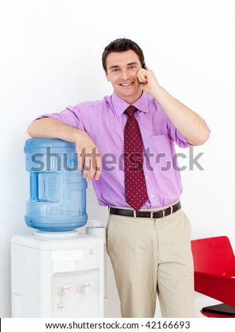 Businessman on phone by the watercooler in the office - stock photo
