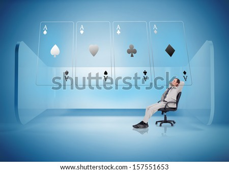 Businessman on swivel chair looking at holographic cards in blue light - stock photo