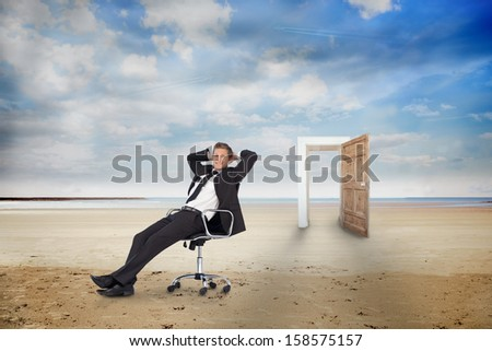 Businessman on swivel chair on the beach with wooden door - stock photo