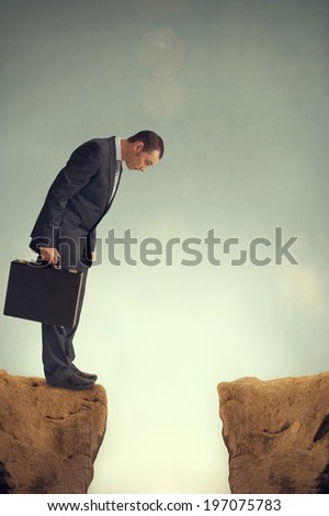 businessman on the edge of a ravine - stock photo