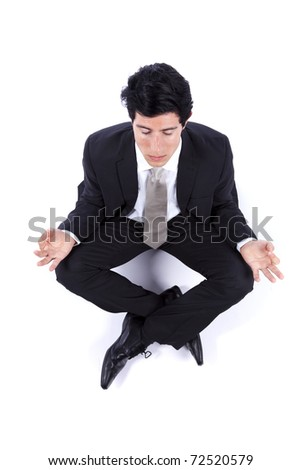Businessman on the floor doing yoga to relax - stock photo