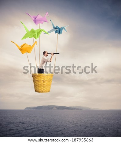 Businessman on the hot-air bslloon looking for new business - stock photo