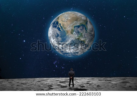 "Businessman on the Moon looking at the Earth planet ""Elements of this image furnished by NASA"" - stock photo"