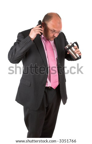 Businessman on the phone looking shocked because he has just spilled some of the coffee from his mug - stock photo