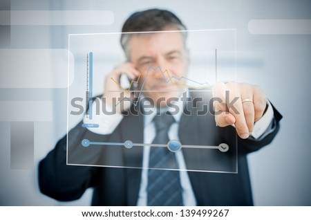 Businessman on the phone using futuristic touchscreen to view graph - stock photo