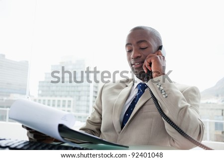 Businessman on the phone while reading a document in his office - stock photo