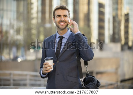 Businessman on the phone with office buildings in the background - stock photo